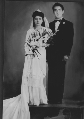 Keytlin's abula (left) next to her abuelo (right) posing for their wedding picture. Both in weeding attire. This is a black and white photo.