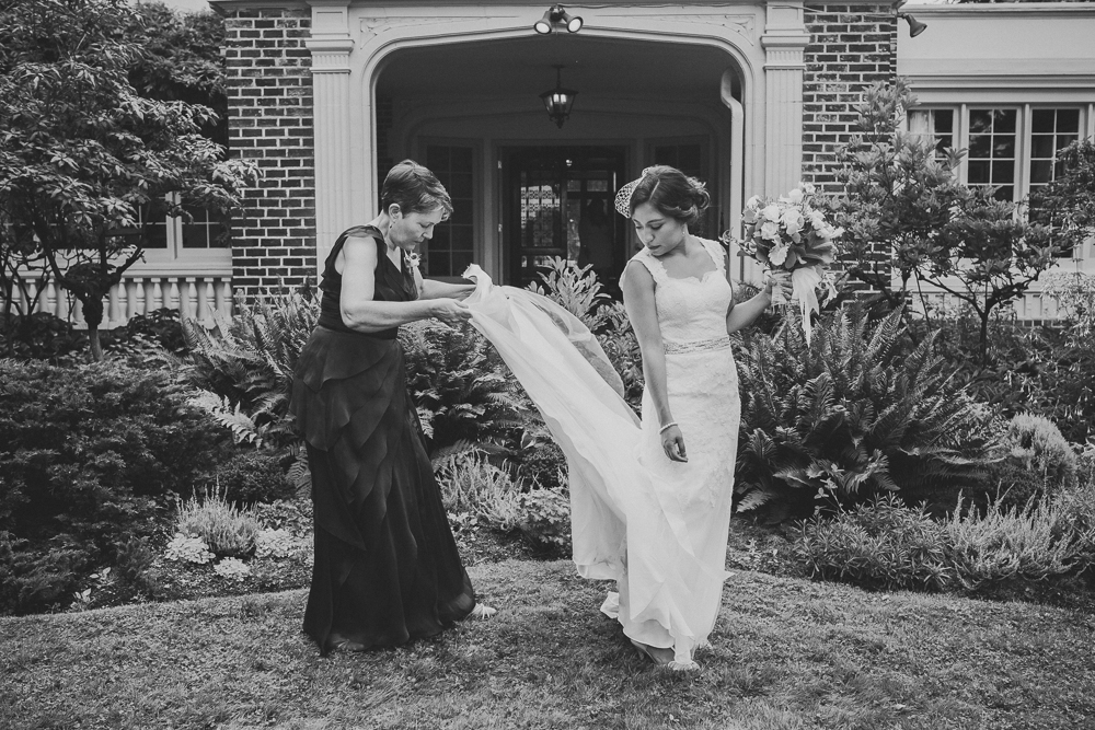 Keitlyn's weeding day. Photo Hollin Brodeur Keitlyn's mom is arranging her wedding dress while Keitlyn holds her buquet and looks what her mom is doing. This photo is black and wwhite.